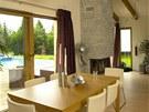 Všechny obytné místnosti jsou orientovány na rohovou dřevěnou terasu s bazénem.