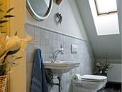 Toaleta pod střechou využívá zkosený prostor, použité obklady a dlažbu dováží