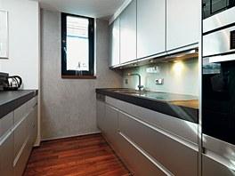 Kuchyně provedená v decentní šedé barevnosti s černou žulovou deskou působí