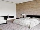 Také ložnice je laděna do stylu etno. Vybavení (postel, křeslo, lampy a
