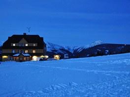 Večer nad Pecí: vlevo Lidická bouda, v dáli Sněžka.