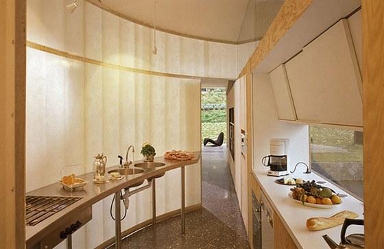 Oblá stěna oddělující kuchyni od obývacího pokoje je z polyesteru.