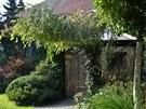Cesta k zimní zahradě je vydlážděná obyčejnými šedivými betonovými kostkami,