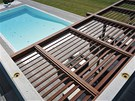 Pohled z terasy v patře. Sezení dole zastiňuje dřevěný slunolam s šikmými