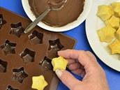Do čistých a suchých formiček nalijte trochu čokolády a upečené kousky vtlačte