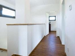Otevřené schodiště propojuje obývací pokoj s chodbou v patře. Horizontální okno