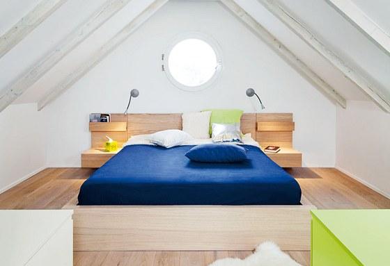 Ložnice rodičů v horním patře s kulatým oknem do zahrady. Nasvícená a bílou