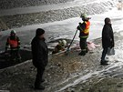 Hasi�i s pomoc� norn� st�ny zabra�uj� �niku nafty v potoce.