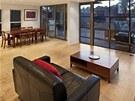 Obývací pokoj s okny vedoucími na terasu s grilem a bazénem