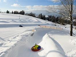 Snowtubing, v pozadí tratě Beneckého kolečka