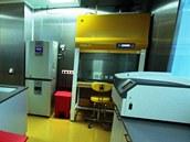 Prostory laboratoře s pracovním boxem vpravo vzadu. Stěny z nezer oceli se