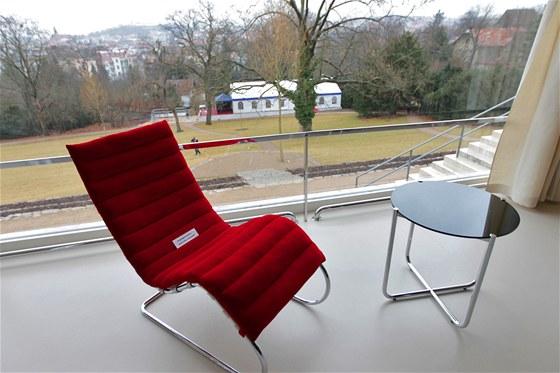 Červené chaise longue v obývacím pokoji s výhledem do zahrady