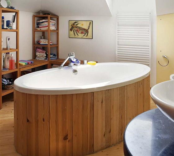 V koupelně vládnou přírodní dřevo a oválné tvary. Podlaha a vana jsou obloženy