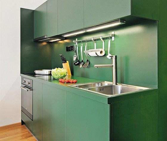 Barevné sjednocení skříněk s obkladem stěny a kuchyňskou deskou je originální a