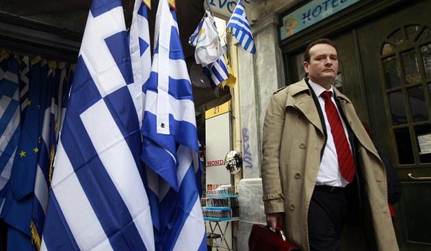 Mu� jde po ulici kolem kiosku prodávajícího �ecké vlajky.