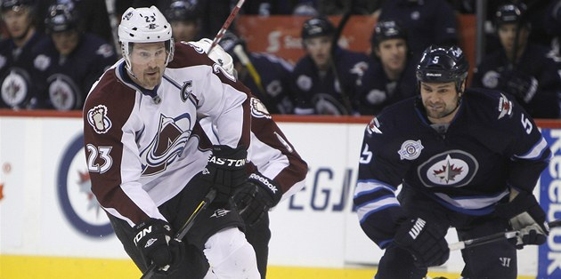 Coloradský kapitán Milan Hejduk (vlevo) sledovaný Markem Stuartem z Winnipegu.