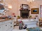 Z honosné koupelny s krbem se vchází do šatny a ložnice.