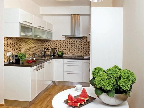 Bílou kuchyňskou linku zvýrazňuje pestrá mozaika, která je v barevném souladu s