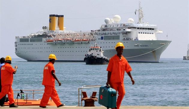 Výletní loď Costa Allegra se blíží do seychelského přístavu tažena malou