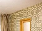 Elegantní kombinaci béžových a krémových tónů oživuje tapeta ve zlaté barvě s