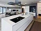 Společná obývací část domu má velkorysé dimenze. Kuchyni z bíle lakovaných MDF