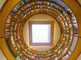 Domácí pracovna je osvětlena stropním oknem. Pod ním je knihovna.