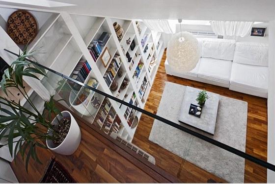 Knihovna je vystavěna po celé jedné stěně a kromě ukládání knih slouží také pro