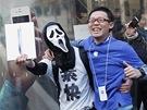 Mladík v masce Anonymous slaví společně s přáteli před prodejnou Apple v Tokiu