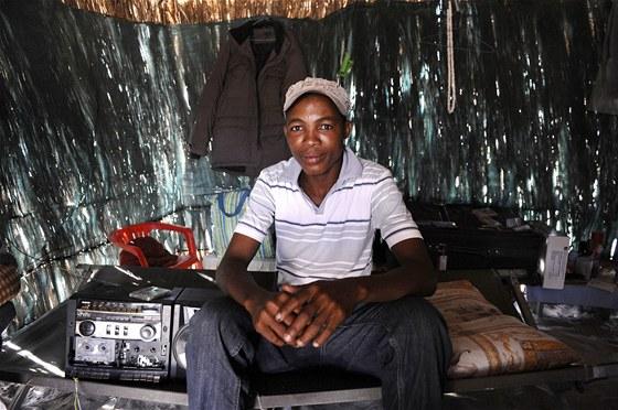 Mladý křovák poslouchá hudbu v tradiční chatrči ve vesnici Molapo v Kalahari.