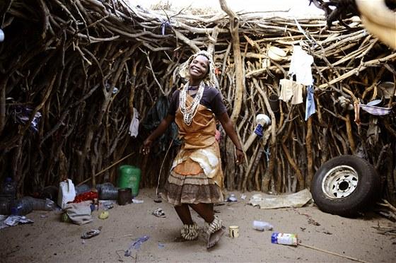 Žena tančí v tradiční chatrči ve vesnici Molapo v Kalahari.