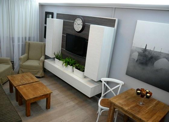 Plochy televizor i skříňky zavěsili designéři na panel s kolejničkami.