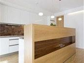 Kuchyňská linka, vyrobená z bíle lakovaných MDF desek, se skrývá za barovým