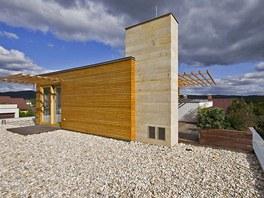 Část střechy tvoří dřevěná terasa, většinu plochy pokrývá kačírek, komínové