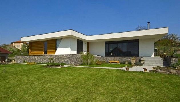 Výrazným architektonickým znakem domu je přesahující střecha a bílá atika,