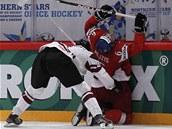 VRA�EN� NA HRAZEN�. Loty�sk� hokejista Oskars Bartulis tvrd� atakuje u mantinelu �esk�ho obr�nce Tom�e Moj��e.