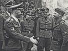 ��f SS Heinrich Himmler se v Mauthausenu p�ijel pozdravit s velitelem t�bora George Bachmayerem. Himmler se na sn�mku zdrav� s jedn�m z m�stn�ch zabij�k�. �Je nep��pustn�, aby str�n� poci�oval s�nep��telem jak�koliv soucit. Pro slabochy nen� v��ad�ch str�c� m�sto a m�-li n�kdo s�v�zni slitov�n�, m�l by co nejrychleji odej�t do kl�tera,� ��kal pohlav�r SS.