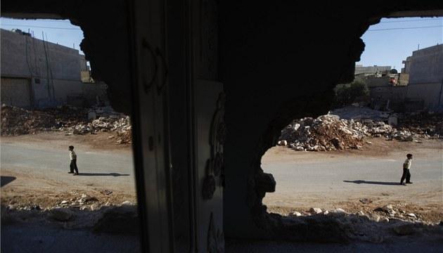 Syrský chlapec krá�í kolem rozbombardovaných dom� ve m�st� Taftanaz, nedaleko