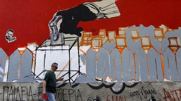 �ek prochází v Aténách kolem opu�t�né budovy s grafitti odkazujícím na