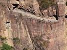 Vinou se po vysokohorských srázech tisíce metrů nad mořem. Některé jsou tak úzké, že dvě vozidla by vedle sebe neprojela. Na snímku vidíte 1 250 metrů dlouhou cestu klikatící se po skalním útesu, která je jedinou spojnicí odlehlé vesnice Kuo-liang v čínské provincii Che-nan. Stezka, která se vine ve skalách ve výšce 119 metrů nad zemí, je výsledkem úmorné pětileté dřiny třinácti místních mladých farmářů.