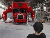 Výtvarník David Černý sedí před svým dílem - londýnským autobusem přestavěným na pohyblivou skulpturu.