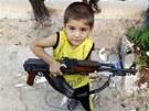 Syrský chlapec z Azázu nedaleko Aleppa si hraje s kalašnikovem svého otce (5. srpna 2012)