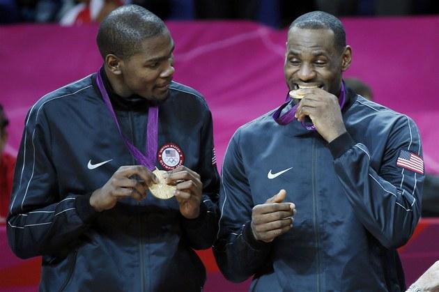 Americký basketbalista Lebron James (vpravo) kou�e do zlaté olympijské medaile,