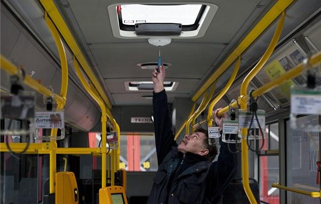 Jeden z pracovník� dopravního podniku ukazuje nainstalovanou kameru v autobuse