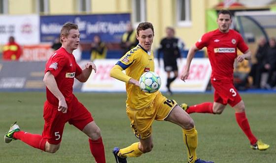 Jihlavský fotbalista Arnold Šimonek (uprostřed) prochází brněnskou obranou.