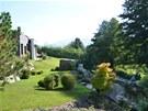 Pohled na dům z terasy nad jezírkem, které je situované do zadní části zahrady, opět dává tušit, že největší důraz domácí kladou na pečlivě udržovaný trávník.