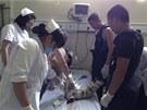 Čínští hasiči a lékaři při záchraně novorozeněte uvázlého v odpadním potrubí.