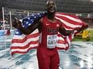 Američan Justin Gatlin slaví s americkou vlajkou stříbro v běhu na 100 metrů.