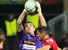 RAKOVAN JE NEJVÝŠ. Slávistický gólman Matej Rakovan (ve fialovém) uchránil míč před dotírajícím plzeňským stoperem Mariánem Čišovským.