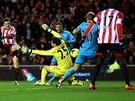 Adam Johnson ze Sunderlandu (vlevo) překonává brankáře Tottenhamu Huga Llorise (ve žlutém).