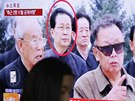 Žena v jihokorejském Soulu prochází kolem obrazovky s archivním snímkem, na kterém je popravený Čang Song-tchek (v kroužku) a bývalý vůdce KLDR Kim Čong-il. (13. prosince 2013)